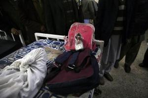 Schoolbags and a shoe are seen beside a girl who was killed in a bomb attack in a Shi'ite Muslim area at a hospital in the Pakistani city of Quetta